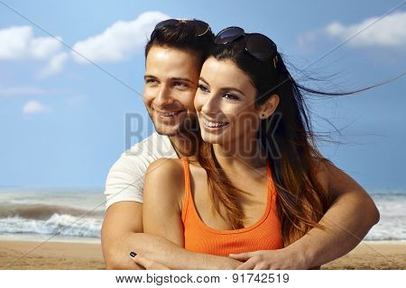 Happy loving couple embracing on the beach, smiling, looking away.