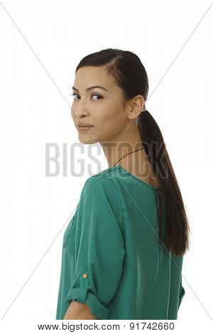 Pretty young Asian girl looking back over shoulder. Portrait.
