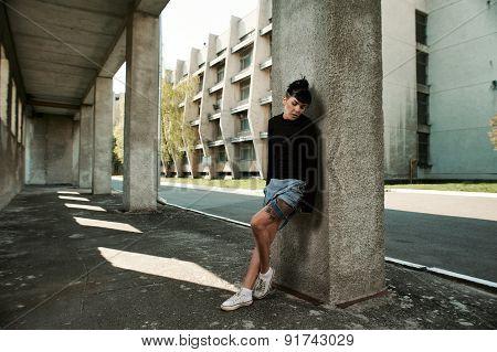 tattooed lady stands in university backyard