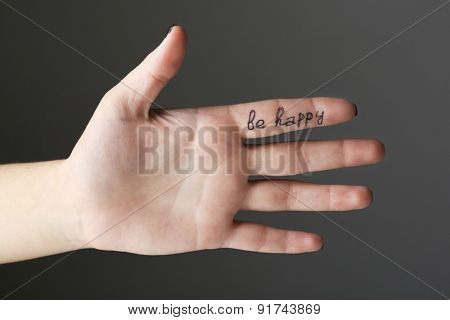 Female hand with written message on gray background
