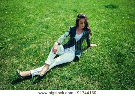 elegant young woman with sunglasses, green jacket,  white pants and high heel shoes sit on grass in park, full body shot