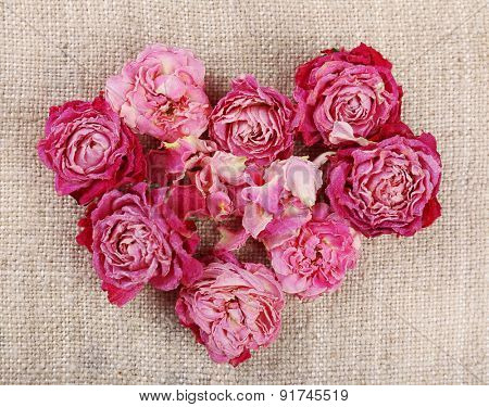 Heart of beautiful dry flowers on sackcloth background