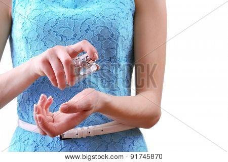 Female hands applying perfume isolated on white