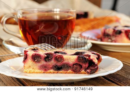 Slice Of Blackberry Pie In White Plate With Cup Of Black Tea