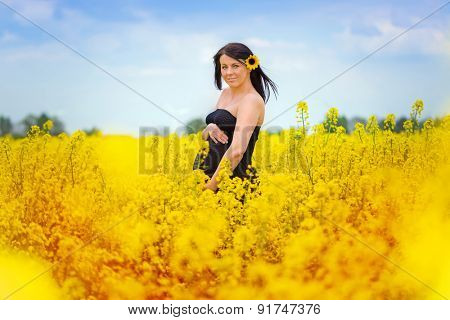 Beautiful pregnant woman portrait in the rapeseed scenery