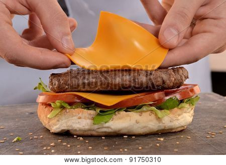 Cook preparing cheese burger.