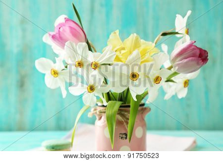 Spring bouquet in vase on color wooden background