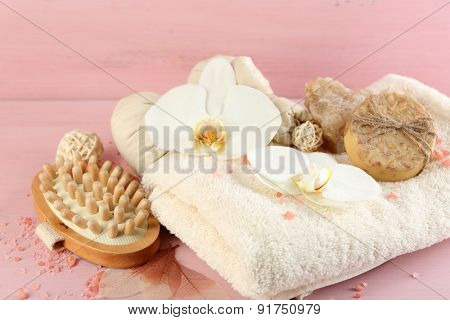 Still life with beautiful blooming orchid flower, spa treatment and pebbles, on color wooden background