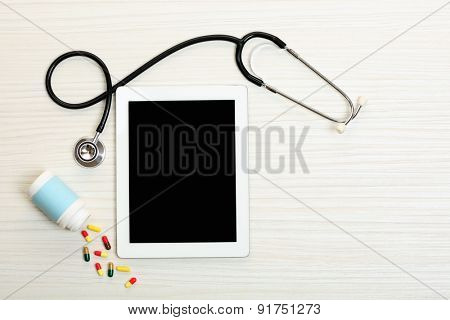 Medical tablet with stethoscope on wooden background