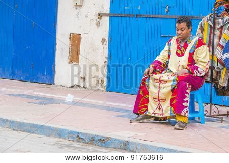 AS-SAWIRA, MOROCCO, APRIL 7, 2015: Seller of clothes waits for customers sitting in front of his stand
