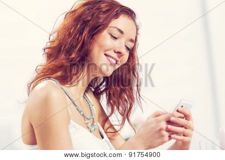 Young and attractive woman sitting in cafe and using cellphone