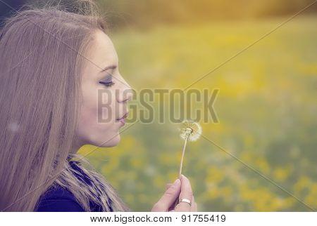 Pretty girl blowing a dandelion
