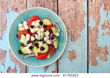 Greek Salad overhead view with rustic wood background