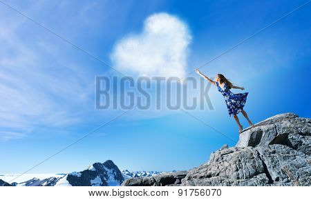 Young romantic woman in summer dress reaching love heart