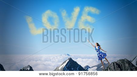 Young romantic woman in summer dress reaching word love