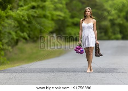A brunette model walking on a road near a field of flowers