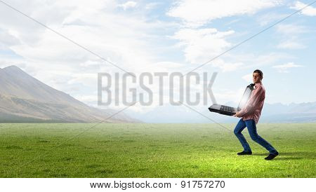 Young man in casual carrying big laptop in hands