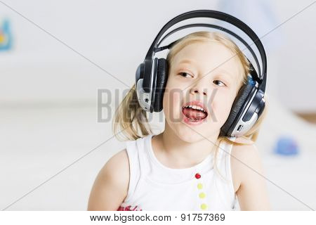 Cute adorable girl wearing headphones and enjoying music