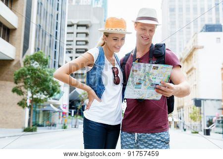 Happy young couple as tourists with a map