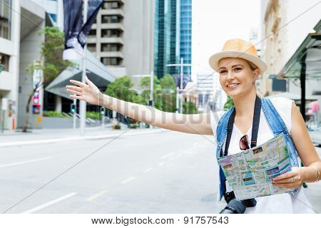 Female tourist calling for a taxi in the city