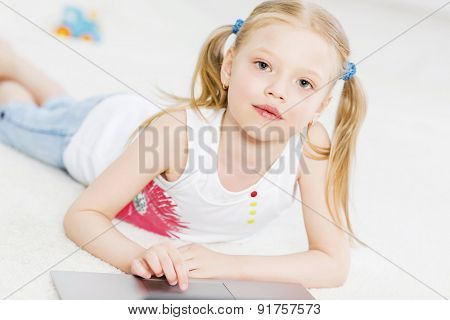 Cute girl laying on the floor and play at laptop