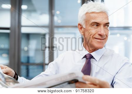 Businessman in office with newspaper