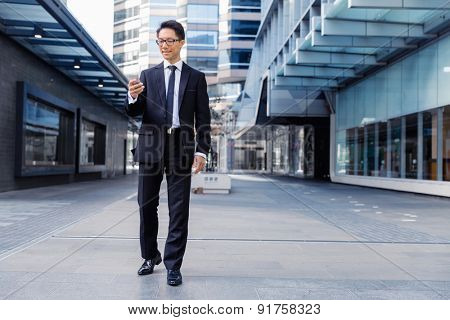 Businessman in city walking and holding his mobile