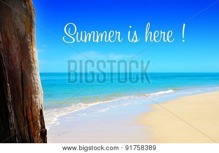 Summer Is Here Text Over Wide Sandy Beach With Blue Skies
