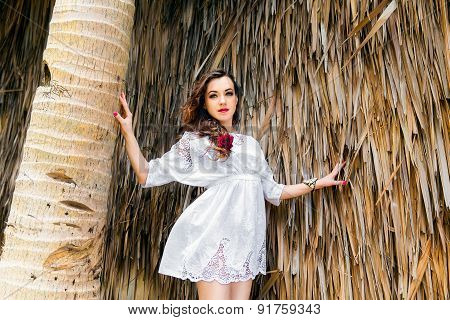 Happy Young Brunette In White Dress Sianding At The Huts Of Palm Leaves On A Tropical Beach. Summer