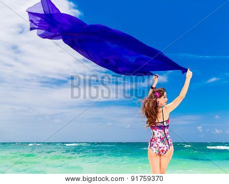 Happy Young Brunette In A Swimsuit Dancing With A Purple Cloth On A Tropical Beach. Blue Sea And Isl