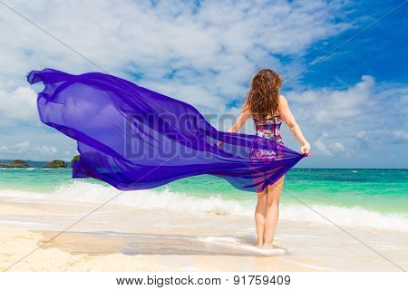 Happy Young Brunette In A Swimsuit Dancing With A Purple Cloth On A Tropical Beach.