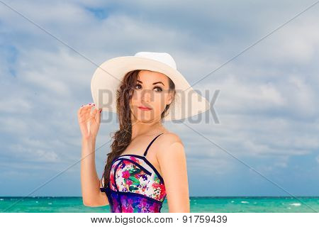 Young Beautiful Girl In A Straw White Hat On The Beach Of A Tropical Island. Summer Vacation Concept