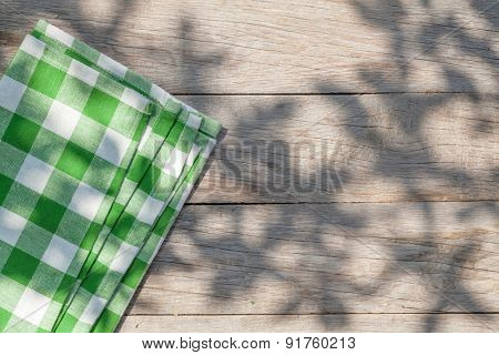 Empty wooden garden table with tablecloth. Top view with copy space