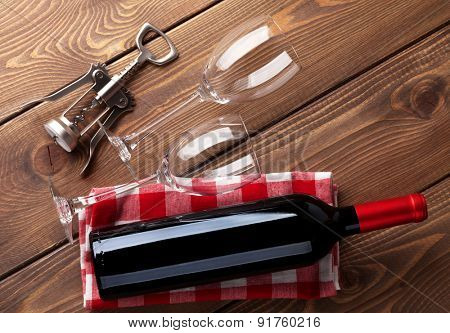 Red wine bottle, glasses and corkscrew on wooden table background. Top view