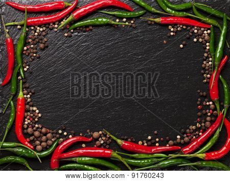 Chili pepper and peppercorn on black stone table with copy space