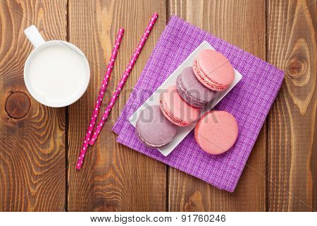 Colorful macaron cookies and cup of milk on wooden table background