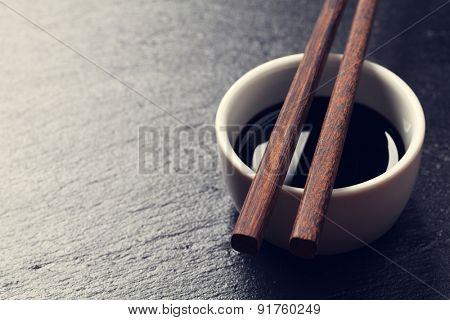 Japanese sushi chopsticks over soy sauce bowl on black stone background. Top view with copy space. Toned