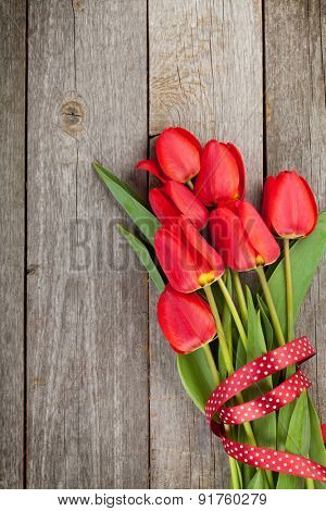 Fresh red tulips bouquet over wooden table background with copy space