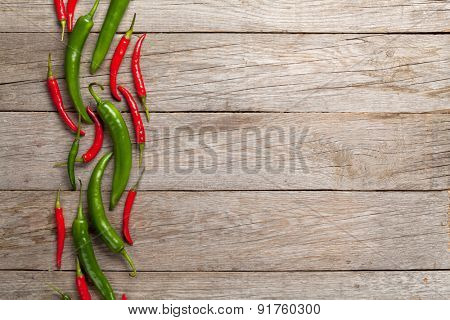 Colorful chili peppers on wooden table with copy space