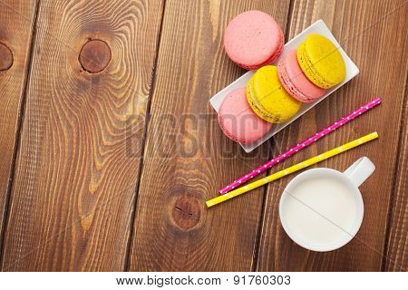 Colorful macaron cookies and cup of milk on wooden table background with copy space