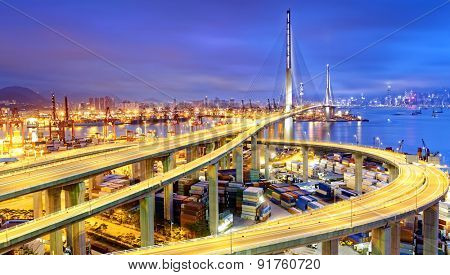 Container Cargo freight ship with working crane bridge in shipyard under Stonecutters highway bridge at sunset for Logistic Import Export, Hong kong