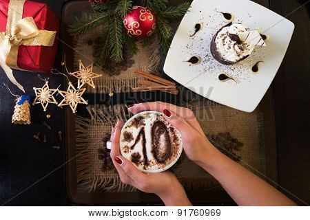 Hands holding mug of coffee with ten signs, close-up, on new year background