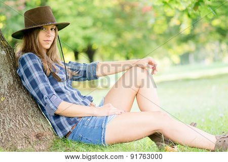 Cute cowgirl restung under the tree