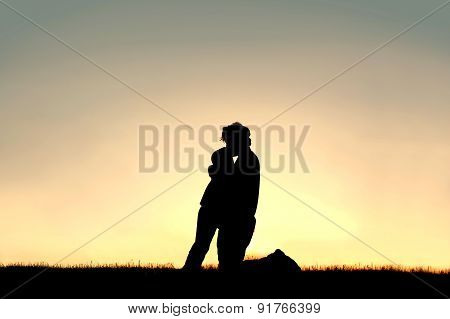 Silhouette Of Father Lovingly Kissing Child On Forehead At Sunset