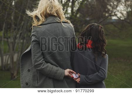 Two Girls Holding A Heart In Its Hands
