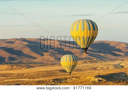 Hot air balloons flying over Cappadocia near Goreme at sunrise, Turkey