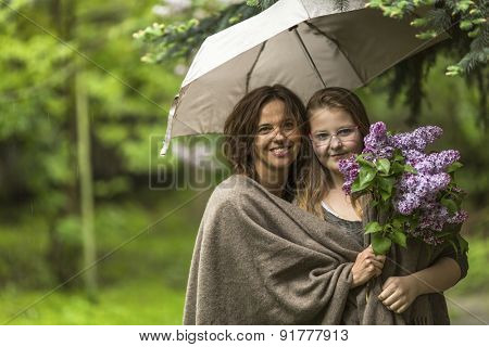Mother with her daughter in the Park in the rain together under an umbrella.