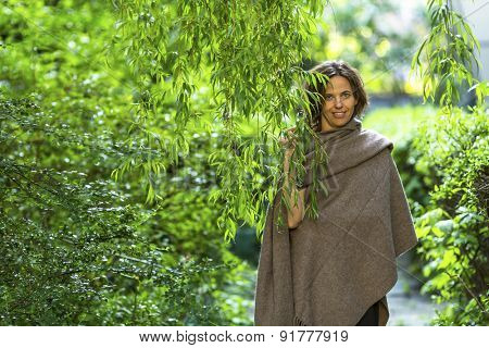 Young charming woman in the Park among the green trees.