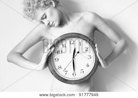 Gentle curly girl with big clock in hands. Black and white photo.