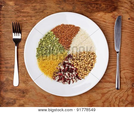 Plate With Different Cereals And Garnish On Table.